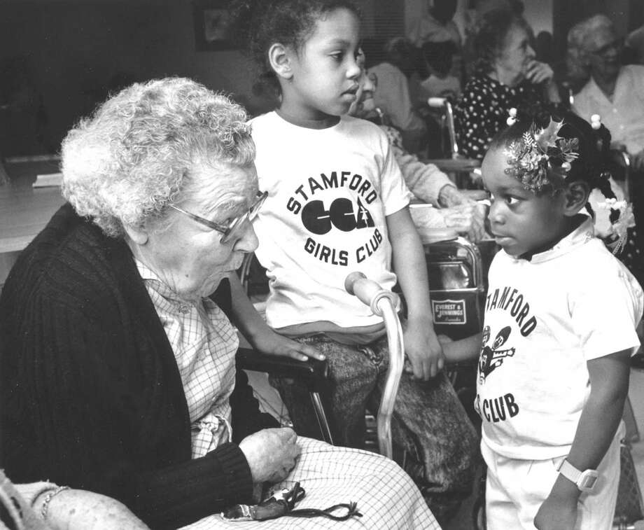After singing Christmas carols for residents at Cortland Gardens on Dec. 17, 1987, members of the Stamford Girls Club talked with the senior residents. Barbara Hodenson (left) talks with 8-year-old Danielle Barksdale (center) and Stacy Powell, aged 4. Photo: Advocate