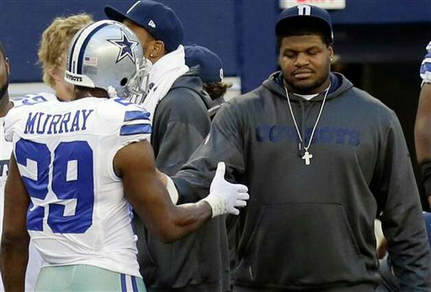 Josh Brent (right) is greeted by DeMarco Murray on the sideline Sunday. According to reports, Brent will not be allowed on the field again this season. Photo: LM Otero, Associated Press / AP