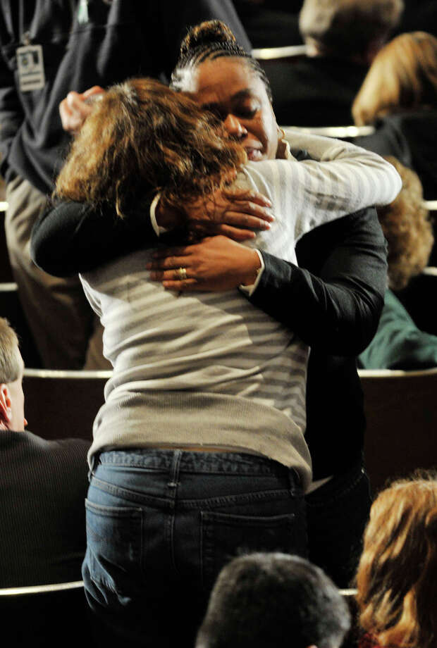 People console each other before President Barack Obama speaks at the Newtown High School auditorium on Sunday, Dec. 16, 2012. Photo: Jason Rearick / The News-Times