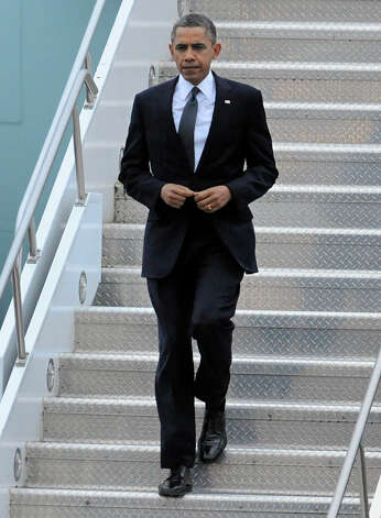 President Obama arrives at the Bradley Air National Guard Base in East Granby, Conn., Sunday, Dec. 16, 2012. The President is in Connecticut to attend a vigil for the victims of the Sandy Hook Elementary School shooting where 26 people, including 20 children, were killed Friday. (AP Photo/Jessica Hill) Photo: AP