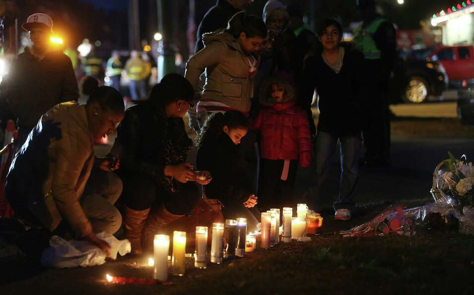 NEWTOWN, CT - DECEMBER 15: Mourners gather at a makeshift memorial following the mass shooting at Sa