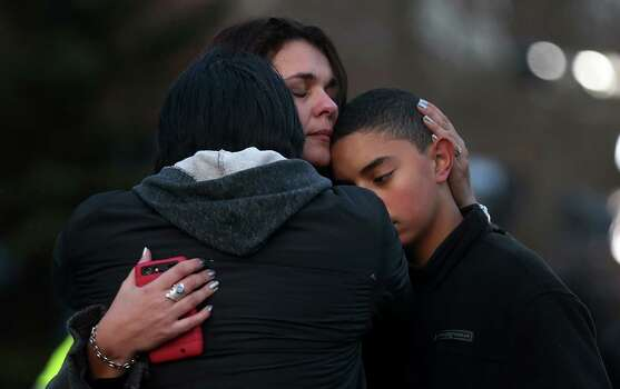 NEWTOWN, CT - DECEMBER 15:  (L to R) Lucas, Kelly and Michael DaSilva embrace at a makeshift memorial near the school following the mass shooting at Sandy Hook Elementary School on December 15, 2012 in Newtown, Connecticut. Twenty six people were shot dead, including twenty children, after a gunman identified as Adam Lanza opened fire in the school. Lanza also reportedly had committed suicide at the scene. A 28th person, believed to be Nancy Lanza was found dead in a house in town, was also believed to have been shot by Adam Lanza.  (Photo by Mario Tama/Getty Images) Photo: Mario Tama, Getty Images / Getty Images