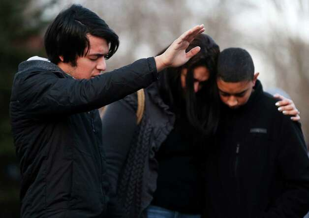 NEWTOWN, CT - DECEMBER 15:  (L to R) Lucas, Kelly and Michael DaSilva pray and embrace at a makeshift memorial following the mass shooting at Sandy Hook Elementary School near the school on December 15, 2012 in Newtown, Connecticut. Twenty six people were shot dead, including twenty children, after a gunman identified as Adam Lanza opened fire in the school. Lanza also reportedly had committed suicide at the scene. A 28th person, believed to be Nancy Lanza was found dead in a house in town, was also believed to have been shot by Adam Lanza.  (Photo by Mario Tama/Getty Images) Photo: Mario Tama, Getty Images / Getty Images