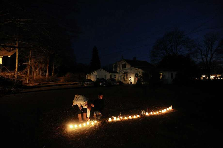 NEWTOWN, CT - DECEMBER 15: People light a row of candles honoring each shooting victim following the mass shooting at Sandy Hook Elementary School on December 15, 2012 in Newtown, Connecticut. Twenty six people were shot dead, including twenty children, after a gunman identified as Adam Lanza opened fire in the school. Lanza also reportedly had committed suicide at the scene. A 28th person, believed to be Nancy Lanza was found dead in a house in town, was also believed to have been shot by Adam Lanza.  (Photo by Mario Tama/Getty Images) Photo: Mario Tama, Getty Images / Getty Images