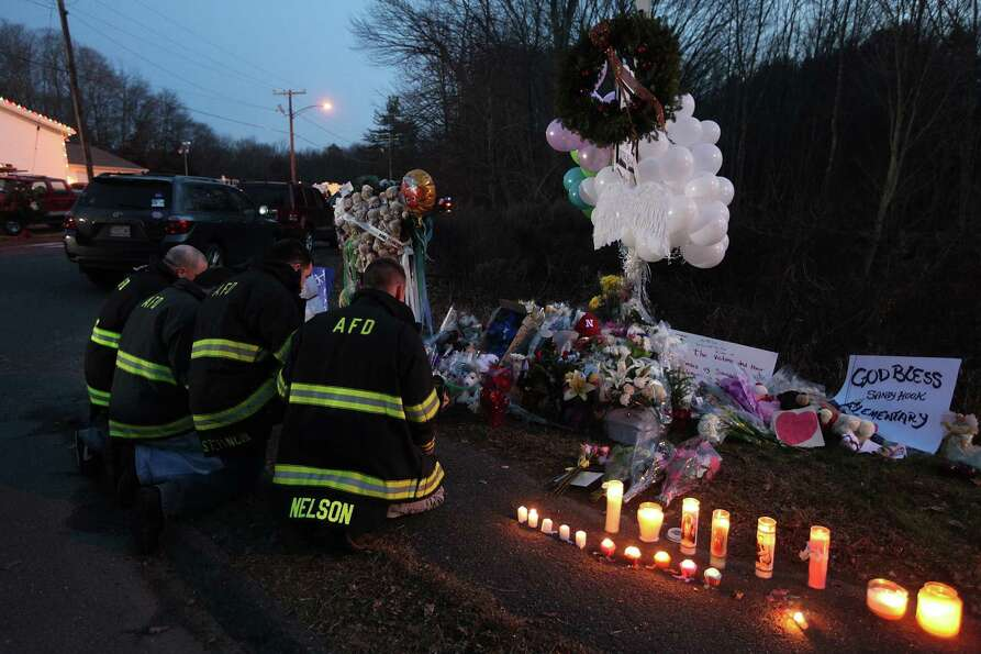 NEWTOWN, CT - DECEMBER 15: Firefighters kneel to pay their respects at a makeshift memorial near the