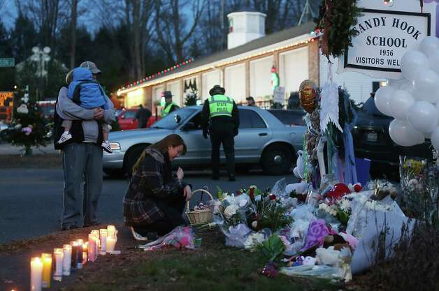 NEWTOWN, CT - DECEMBER 15: People gather at a makeshift memorial near the school following the mass shooting at Sandy Hook Elementary School on December 15, 2012 in Newtown, Connecticut. Twenty six people were shot dead, including twenty children, after a gunman identified as Adam Lanza opened fire in the school. Lanza also reportedly had committed suicide at the scene. A 28th person, believed to be Nancy Lanza was found dead in a house in town, was also believed to have been shot by Adam Lanza.  (Photo by Mario Tama/Getty Images) Photo: Mario Tama, Getty Images / Getty Images