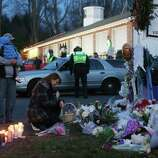 NEWTOWN, CT - DECEMBER 15: People gather at a makeshift memorial near the school following the mass shooting at Sandy Hook Elementary School on December 15, 2012 in Newtown, Connecticut. Twenty six people were shot dead, including twenty children, after a gunman identified as Adam Lanza opened fire in the school. Lanza also reportedly had committed suicide at the scene. A 28th person, believed to be Nancy Lanza was found dead in a house in town, was also believed to have been shot by Adam Lanza.  (Photo by Mario Tama/Getty Images)