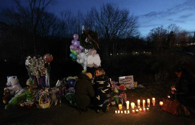 NEWTOWN, CT - DECEMBER 15:  Mourners kneel at a makeshift memorial near the school following the mass shooting at Sandy Hook Elementary School on December 15, 2012 in Newtown, Connecticut. Twenty six people were shot dead, including twenty children, after a gunman identified as Adam Lanza opened fire in the school. Lanza also reportedly had committed suicide at the scene. A 28th person, believed to be Nancy Lanza was found dead in a house in town, was also believed to have been shot by Adam Lanza.  (Photo by Mario Tama/Getty Images) Photo: Mario Tama, Getty Images / Getty Images