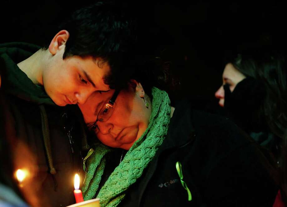 STRATFORD, CT - DECEMBER 15: Donna Soto (R), mother of Victoria Soto, the first-grade teacher at Sandy Hook Elementary School who was shot and killed while protecting her students, leans on her son Matthew while mourning their loss at a candlelight vigil in honor of Victoria at Stratford High School on December 15, 2012 in Stratford, Connecticut. Twenty-six people were shot dead, including twenty children, after a gunman identified as Adam Lanza opened fire in the school. Lanza also reportedly had committed suicide at the scene. A 28th person, believed to be Nancy Lanza was found dead in a house in town, was also believed to have been shot by Adam Lanza. (Photo by Jared Wickerham/Getty Images) Photo: Jared Wickerham, Getty Images / Getty Images
