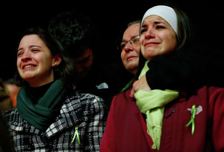 STRATFORD, CT - DECEMBER 15: Donna Soto (C), mother of Victoria Soto, the first-grade teacher at Sandy Hook Elementary School who was shot and killed while protecting her students, hugs her daughter Karly (R) while mourning their loss with another of Victoria's siblings, Jillian Soto (L), at a candlelight vigil at Stratford High School on December 15, 2012 in Stratford, Connecticut. Twenty-six people were shot dead, including twenty children, after a gunman identified as Adam Lanza opened fire in the school. Lanza also reportedly had committed suicide at the scene. A 28th person, believed to be Nancy Lanza was found dead in a house in town, was also believed to have been shot by Adam Lanza. (Photo by Jared Wickerham/Getty Images) Photo: Jared Wickerham, Getty Images / Getty Images