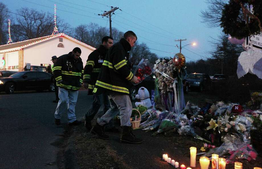 NEWTOWN, CT - DECEMBER 15:  Firefighters walk to pay their respects at a makeshift memorial near the school following the mass shooting at Sandy Hook Elementary School on December 15, 2012 in Newtown, Connecticut. Twenty six people were shot dead, including twenty children, after a gunman identified as Adam Lanza opened fire in the school. Lanza also reportedly had committed suicide at the scene. A 28th person, believed to be Nancy Lanza was found dead in a house in town, was also believed to have been shot by Adam Lanza.  (Photo by Mario Tama/Getty Images) Photo: Mario Tama, Getty Images / Getty Images