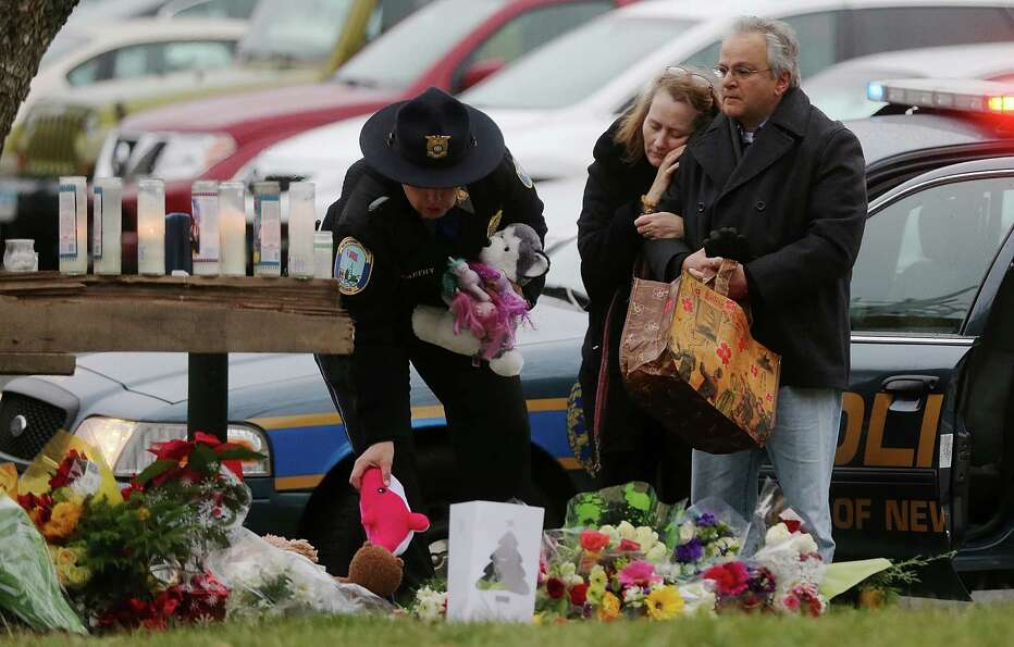 NEWTOWN, CT - DECEMBER 16:  Mourners including a Newtown Police officer (L) gather at a makeshift me