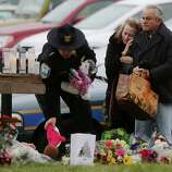 NEWTOWN, CT - DECEMBER 16:  Mourners including a Newtown Police officer (L) gather at a makeshift memorial outside St. Rose of Lima Roman Catholic Church during the first day of Sunday services following the mass shooting at Sandy Hook Elementary School on December 16, 2012 in Newtown, Connecticut.  Twenty six people were shot dead, including twenty children, after a gunman identified as Adam Lanza in news reports opened fire in the school. Lanza also reportedly had committed suicide at the scene.  (Photo by Mario Tama/Getty Images)