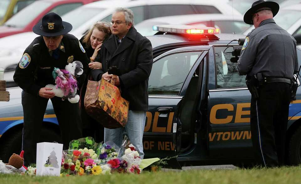 NEWTOWN, CT - DECEMBER 16:  Mourners including a Newtown Police officers gather at a makeshift memor