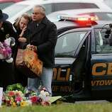 NEWTOWN, CT - DECEMBER 16:  Mourners including a Newtown Police officers gather at a makeshift memorial outside St. Rose of Lima Roman Catholic Church during the first day of Sunday services following the mass shooting at Sandy Hook Elementary School on December 16, 2012 in Newtown, Connecticut.  Twenty six people were shot dead, including twenty children, after a gunman identified as Adam Lanza in news reports opened fire in the school. Lanza also reportedly had committed suicide at the scene.  (Photo by Mario Tama/Getty Images)