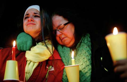 STRATFORD, CT - DECEMBER 15: Donna Soto (R), mother of Victoria Soto, the first-grade teacher at Sandy Hook Elementary School who was shot and killed while protecting her students, hugs her daughter Karly while mourning their loss at a candlelight vigil in honor of Victoria at Stratford High School on December 15, 2012 in Stratford, Connecticut. Twenty-six people were shot dead, including twenty children, after a gunman identified as Adam Lanza opened fire in the school. Lanza also reportedly had committed suicide at the scene. A 28th person, believed to be Nancy Lanza was found dead in a house in town, was also believed to have been shot by Adam Lanza. (Photo by Jared Wickerham/Getty Images) Photo: Jared Wickerham, Getty Images / Getty Images