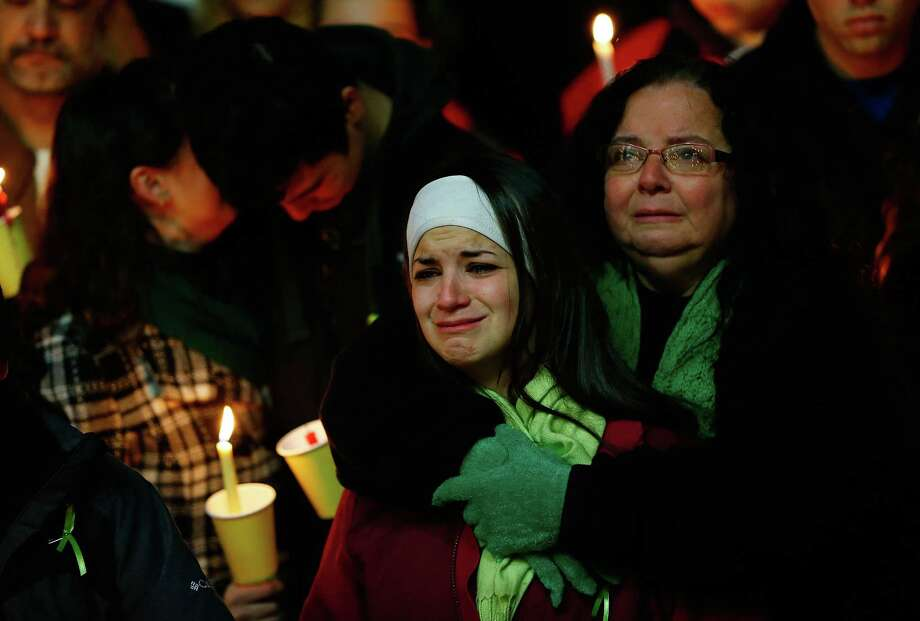 STRATFORD, CT - DECEMBER 15: Donna Soto (R), mother of Victoria Soto, the first-grade teacher at Sandy Hook Elementary School who was shot and killed while protecting her students, hugs her daughter Karly (second from right) while mourning their loss with Victoria's other two siblings, Jillian (far left) and Matthew Soto (second from left), at a candlelight vigil at Stratford High School on December 15, 2012 in Stratford, Connecticut. Twenty-six people were shot dead, including twenty children, after a gunman identified as Adam Lanza opened fire in the school. Lanza also reportedly had committed suicide at the scene. A 28th person, believed to be Nancy Lanza was found dead in a house in town, was also believed to have been shot by Adam Lanza. (Photo by Jared Wickerham/Getty Images) Photo: Jared Wickerham, Getty Images / Getty Images