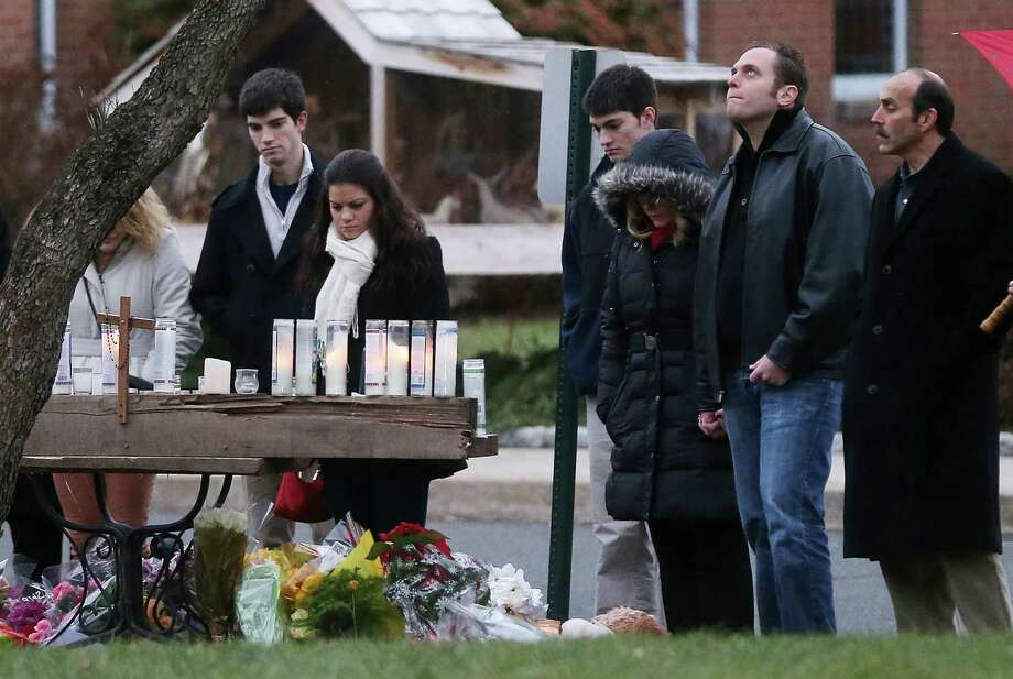 NEWTOWN, CT - DECEMBER 16:  Mourners view a makeshift memorial outside St. Rose of Lima Roman Catholic Church during the first day of Sunday services following the mass shooting at Sandy Hook Elementary School on December 16, 2012 in Newtown, Connecticut.  Twenty six people were shot dead, including twenty children, after a gunman identified as Adam Lanza in news reports opened fire in the school. Lanza also reportedly had committed suicide at the scene.  (Photo by Mario Tama/Getty Images) Photo: Mario Tama, Getty Images / Getty Images