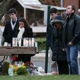 NEWTOWN, CT - DECEMBER 16:  Mourners view a makeshift memorial outside St. Rose of Lima Roman Catholic Church during the first day of Sunday services following the mass shooting at Sandy Hook Elementary School on December 16, 2012 in Newtown, Connecticut.  Twenty six people were shot dead, including twenty children, after a gunman identified as Adam Lanza in news reports opened fire in the school. Lanza also reportedly had committed suicide at the scene.  (Photo by Mario Tama/Getty Images)