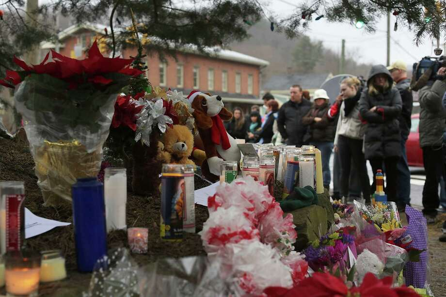 NEWTOWN, CT - DECEMBER 16: Residents reflect at a memorial down the street from the Sandy Hook School December 16, 2012 in Newtown, Connecticut. Twenty-six people were shot dead, including twenty children, after a gunman identified as Adam Lanza opened fire at Sandy Hook Elementary School. Lanza also reportedly had committed suicide at the scene. A 28th person, believed to be Nancy Lanza, found dead in a house in town, was also believed to have been shot by Adam Lanza.  (Photo by Spencer Platt/Getty Images) Photo: Spencer Platt, Getty Images / Getty Images