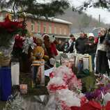 NEWTOWN, CT - DECEMBER 16: Residents reflect at a memorial down the street from the Sandy Hook School December 16, 2012 in Newtown, Connecticut. Twenty-six people were shot dead, including twenty children, after a gunman identified as Adam Lanza opened fire at Sandy Hook Elementary School. Lanza also reportedly had committed suicide at the scene. A 28th person, believed to be Nancy Lanza, found dead in a house in town, was also believed to have been shot by Adam Lanza.  (Photo by Spencer Platt/Getty Images)