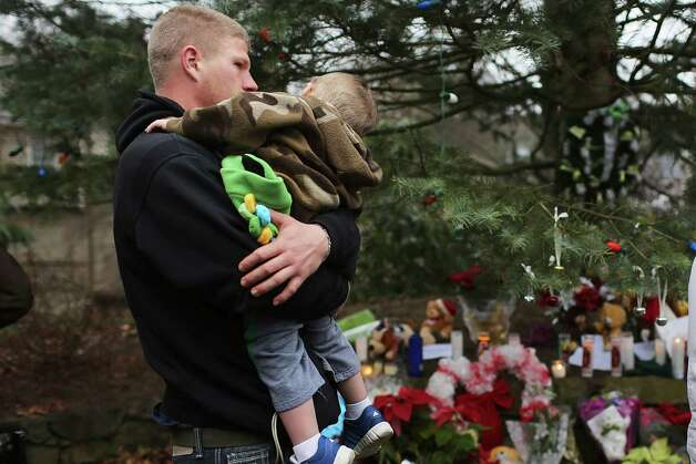 NEWTOWN, CT - DECEMBER 16: Robert Klein holds his son Robbie Jr. at a memorial down the street from the Sandy Hook School December 16, 2012 in Newtown, Connecticut. Twenty-six people were shot dead, including twenty children, after a gunman identified as Adam Lanza opened fire at Sandy Hook Elementary School. Lanza also reportedly had committed suicide at the scene. A 28th person, believed to be Nancy Lanza, found dead in a house in town, was also believed to have been shot by Adam Lanza.  (Photo by Spencer Platt/Getty Images) Photo: Spencer Platt, Getty Images / Getty Images