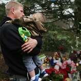 NEWTOWN, CT - DECEMBER 16: Robert Klein holds his son Robbie Jr. at a memorial down the street from the Sandy Hook School December 16, 2012 in Newtown, Connecticut. Twenty-six people were shot dead, including twenty children, after a gunman identified as Adam Lanza opened fire at Sandy Hook Elementary School. Lanza also reportedly had committed suicide at the scene. A 28th person, believed to be Nancy Lanza, found dead in a house in town, was also believed to have been shot by Adam Lanza.  (Photo by Spencer Platt/Getty Images)