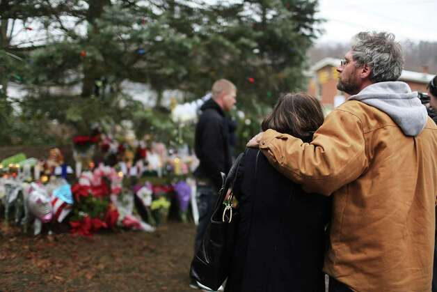 NEWTOWN, CT - DECEMBER 16: A  couple reflects at a memorial down the street from the Sandy Hook School December 16, 2012 in Newtown, Connecticut. Twenty-six people were shot dead, including twenty children, after a gunman identified as Adam Lanza opened fire at Sandy Hook Elementary School. Lanza also reportedly had committed suicide at the scene. A 28th person, believed to be Nancy Lanza, found dead in a house in town, was also believed to have been shot by Adam Lanza.  (Photo by Spencer Platt/Getty Images) Photo: Spencer Platt, Getty Images / Getty Images