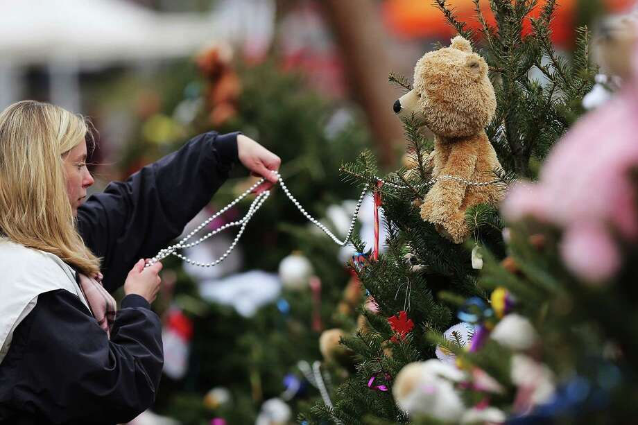 NEWTOWN, CT - DECEMBER 16:  Kat Donohue of Newtown helps to decorate donated Christmas trees placed in front of the  Sandy Hook School December 16, 2012 in Newtown, Connecticut. Twenty-six people were shot dead, including twenty children, after a gunman identified as Adam Lanza opened fire at Sandy Hook Elementary School. Lanza also reportedly had committed suicide at the scene. A 28th person, believed to be Nancy Lanza, found dead in a house in town, was also believed to have been shot by Adam Lanza.  (Photo by Spencer Platt/Getty Images) Photo: Spencer Platt, Getty Images / Getty Images