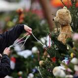 NEWTOWN, CT - DECEMBER 16:  Kat Donohue of Newtown helps to decorate donated Christmas trees placed in front of the  Sandy Hook School December 16, 2012 in Newtown, Connecticut. Twenty-six people were shot dead, including twenty children, after a gunman identified as Adam Lanza opened fire at Sandy Hook Elementary School. Lanza also reportedly had committed suicide at the scene. A 28th person, believed to be Nancy Lanza, found dead in a house in town, was also believed to have been shot by Adam Lanza.  (Photo by Spencer Platt/Getty Images)