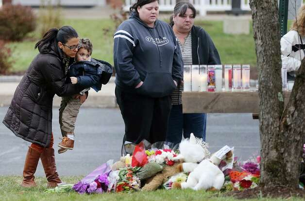 NEWTOWN, CT - DECEMBER 16:  People gather at a makeshift memorial outside St. Rose of Lima Roman Catholic Church during the first day of Sunday services following the mass shooting at Sandy Hook Elementary School on December 16, 2012 in Newtown, Connecticut.  Twenty six people were shot dead, including twenty children, after a gunman identified as Adam Lanza in news reports opened fire in the school. Lanza also reportedly had committed suicide at the scene.  (Photo by Mario Tama/Getty Images) Photo: Mario Tama, Getty Images / Getty Images