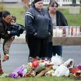 NEWTOWN, CT - DECEMBER 16:  People gather at a makeshift memorial outside St. Rose of Lima Roman Catholic Church during the first day of Sunday services following the mass shooting at Sandy Hook Elementary School on December 16, 2012 in Newtown, Connecticut.  Twenty six people were shot dead, including twenty children, after a gunman identified as Adam Lanza in news reports opened fire in the school. Lanza also reportedly had committed suicide at the scene.  (Photo by Mario Tama/Getty Images)