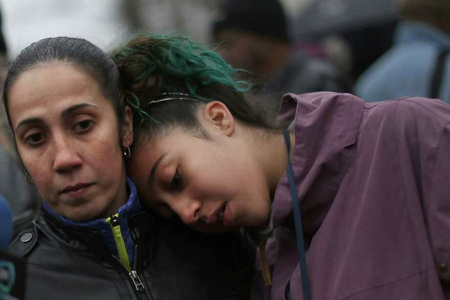 NEWTOWN, CT - DECEMBER 16: Yvette Diaz (left) and her daughter Sienna, both of the Bronx, pause at a memorial down the street from the Sandy Hook School December 16, 2012 in Newtown, Connecticut. Twenty-six people were shot dead, including twenty children, after a gunman identified as Adam Lanza opened fire at Sandy Hook Elementary School. Lanza also reportedly had committed suicide at the scene. A 28th person, believed to be Nancy Lanza, found dead in a house in town, was also believed to have been shot by Adam Lanza.  (Photo by Spencer Platt/Getty Images) Photo: Spencer Platt, Getty Images / Getty Images