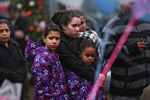 NEWTOWN, CT - DECEMBER 16:  People pause at a memorial in front of the Sandy Hook School December 16, 2012 in Newtown, Connecticut. Twenty-six people were shot dead, including twenty children, after a gunman identified as Adam Lanza opened fire at Sandy Hook Elementary School. Lanza also reportedly had committed suicide at the scene. A 28th person, believed to be Nancy Lanza, found dead in a house in town, was also believed to have been shot by Adam Lanza.  (Photo by Spencer Platt/Getty Images) Photo: Spencer Platt, Getty Images / Getty Images