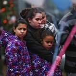 NEWTOWN, CT - DECEMBER 16:  People pause at a memorial in front of the Sandy Hook School December 16, 2012 in Newtown, Connecticut. Twenty-six people were shot dead, including twenty children, after a gunman identified as Adam Lanza opened fire at Sandy Hook Elementary School. Lanza also reportedly had committed suicide at the scene. A 28th person, believed to be Nancy Lanza, found dead in a house in town, was also believed to have been shot by Adam Lanza.  (Photo by Spencer Platt/Getty Images)