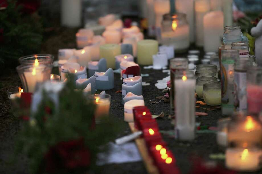 NEWTOWN, CT - DECEMBER 16: Candles are lit at a memorial in front of the Sandy Hook School December 16, 2012 in Newtown, Connecticut. Twenty-six people were shot dead, including twenty children, after a gunman identified as Adam Lanza opened fire at Sandy Hook Elementary School. Lanza also reportedly had committed suicide at the scene. A 28th person, believed to be Nancy Lanza, found dead in a house in town, was also believed to have been shot by Adam Lanza.  (Photo by Spencer Platt/Getty Images) Photo: Spencer Platt, Getty Images / Getty Images