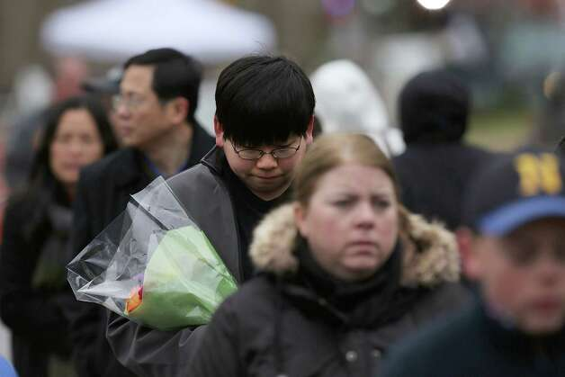 NEWTOWN, CT - DECEMBER 16:  People walk to lay flowers in front of the Sandy Hook School December 16, 2012 in Newtown, Connecticut. Twenty-six people were shot dead, including twenty children, after a gunman identified as Adam Lanza opened fire at Sandy Hook Elementary School. Lanza also reportedly had committed suicide at the scene. A 28th person, believed to be Nancy Lanza, found dead in a house in town, was also believed to have been shot by Adam Lanza.  (Photo by Spencer Platt/Getty Images) Photo: Spencer Platt, Getty Images / Getty Images