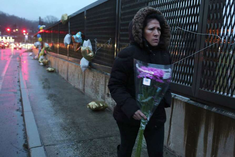 NEWTOWN, CT - DECEMBER 16: A woman walks to lay flowers in front of the Sandy Hook School December 1