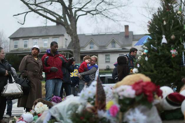 NEWTOWN, CT - DECEMBER 16:  People reflect at a memorial down the street from the Sandy Hook School December 16, 2012 in Newtown, Connecticut. Twenty-six people were shot dead, including twenty children, after a gunman identified as Adam Lanza opened fire at Sandy Hook Elementary School. Lanza also reportedly had committed suicide at the scene. A 28th person, believed to be Nancy Lanza, found dead in a house in town, was also believed to have been shot by Adam Lanza.  (Photo by Spencer Platt/Getty Images) Photo: Spencer Platt, Getty Images / Getty Images