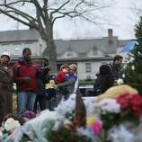 NEWTOWN, CT - DECEMBER 16:  People reflect at a memorial down the street from the Sandy Hook School December 16, 2012 in Newtown, Connecticut. Twenty-six people were shot dead, including twenty children, after a gunman identified as Adam Lanza opened fire at Sandy Hook Elementary School. Lanza also reportedly had committed suicide at the scene. A 28th person, believed to be Nancy Lanza, found dead in a house in town, was also believed to have been shot by Adam Lanza.  (Photo by Spencer Platt/Getty Images)