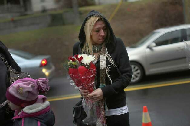 NEWTOWN, CT - DECEMBER 16:  A  woman pauses at a memorial down the street from the Sandy Hook School December 16, 2012 in Newtown, Connecticut. Twenty-six people were shot dead, including twenty children, after a gunman identified as Adam Lanza opened fire at Sandy Hook Elementary School. Lanza also reportedly had committed suicide at the scene. A 28th person, believed to be Nancy Lanza, found dead in a house in town, was also believed to have been shot by Adam Lanza.  (Photo by Spencer Platt/Getty Images) Photo: Spencer Platt, Getty Images / Getty Images