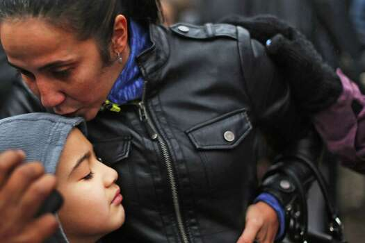 NEWTOWN, CT - DECEMBER 16:  Ty Diaz is kissed by his mother Yvette at a memorial down the street from the Sandy Hook School December 16, 2012 in Newtown, Connecticut. Twenty-six people were shot dead, including twenty children, after a gunman identified as Adam Lanza opened fire at Sandy Hook Elementary School. Lanza also reportedly had committed suicide at the scene. A 28th person, believed to be Nancy Lanza, found dead in a house in town, was also believed to have been shot by Adam Lanza.  (Photo by Spencer Platt/Getty Images) Photo: Spencer Platt, Getty Images / Getty Images