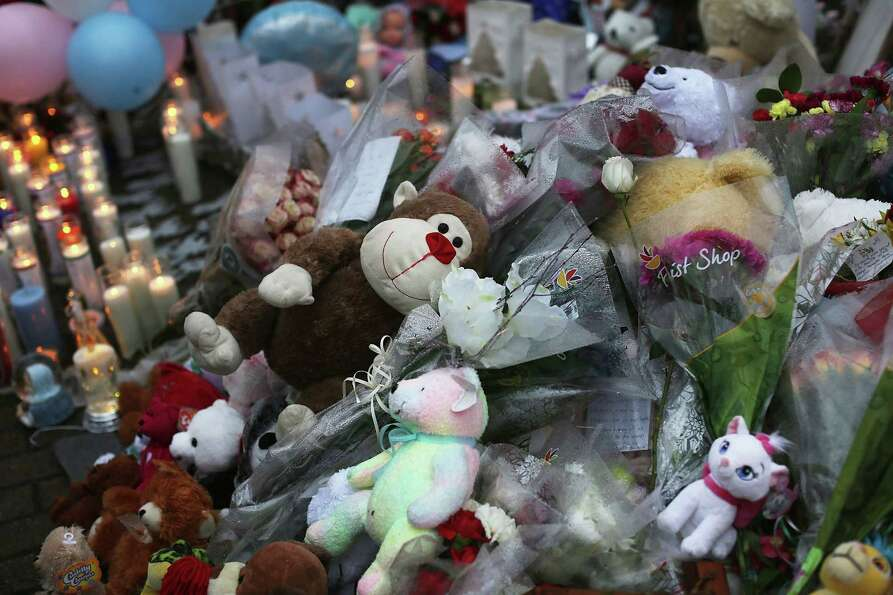 NEWTOWN, CT - DECEMBER 16:  Teddy bears, flowers and candles in memory of those killed, are left at