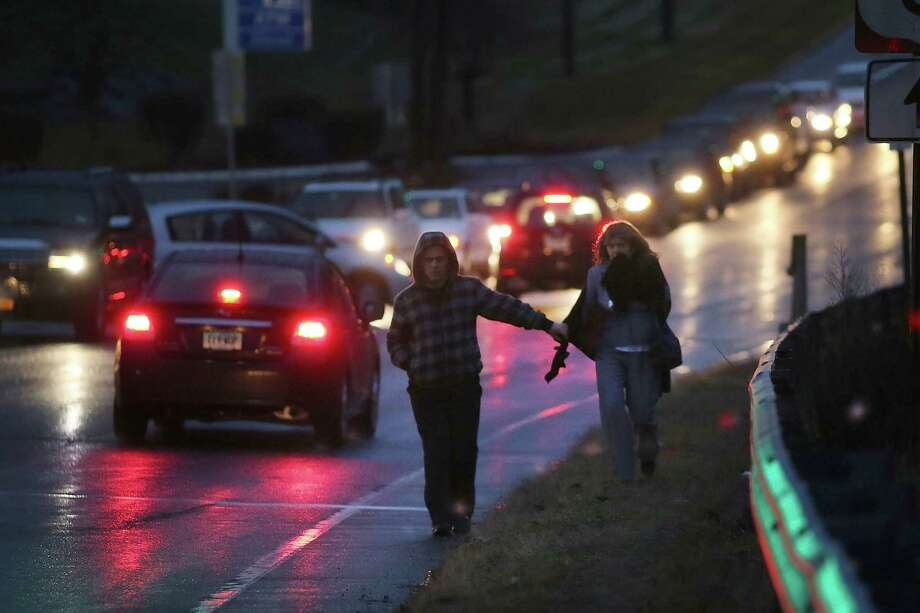 NEWTOWN, CT - DECEMBER 16: People walk to a memorial in front of the Sandy Hook School December 16, 2012 in Newtown, Connecticut. Twenty-six people were shot dead, including twenty children, after a gunman identified as Adam Lanza opened fire at Sandy Hook Elementary School. Lanza also reportedly had committed suicide at the scene. A 28th person, believed to be Nancy Lanza, found dead in a house in town, was also believed to have been shot by Adam Lanza.  (Photo by Spencer Platt/Getty Images) Photo: Spencer Platt, Getty Images / Getty Images