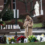 A woman prays at a memorial outside of St. Rose of Lima Church in the Sandy Hook section of Newtown, Conn. on Sunday, Dec. 16, 2012.