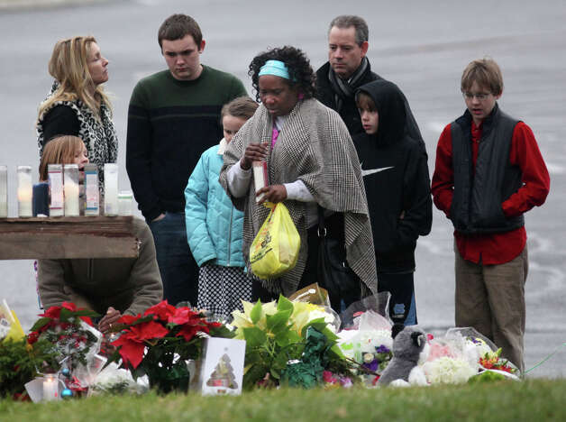 A woman lights a candle at a memorial outside of St. Rose of Lima Church in the Sandy Hook section of Newtown, Conn. on Sunday, Dec. 16, 2012. Photo: BK Angeletti, B.K. Angeletti / Connecticut Post freelance B.K. Angeletti