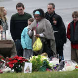 A woman lights a candle at a memorial outside of St. Rose of Lima Church in the Sandy Hook section of Newtown, Conn. on Sunday, Dec. 16, 2012.