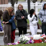 People bring flowers to a memorial outside of St. Rose of Lima Church in the Sandy Hook section of Newtown, Conn. on Sunday, Dec. 16, 2012.