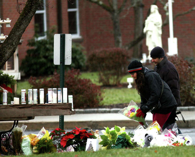 People bring flowers to a memorial outside of St. Rose of Lima Church in the Sandy Hook section of N