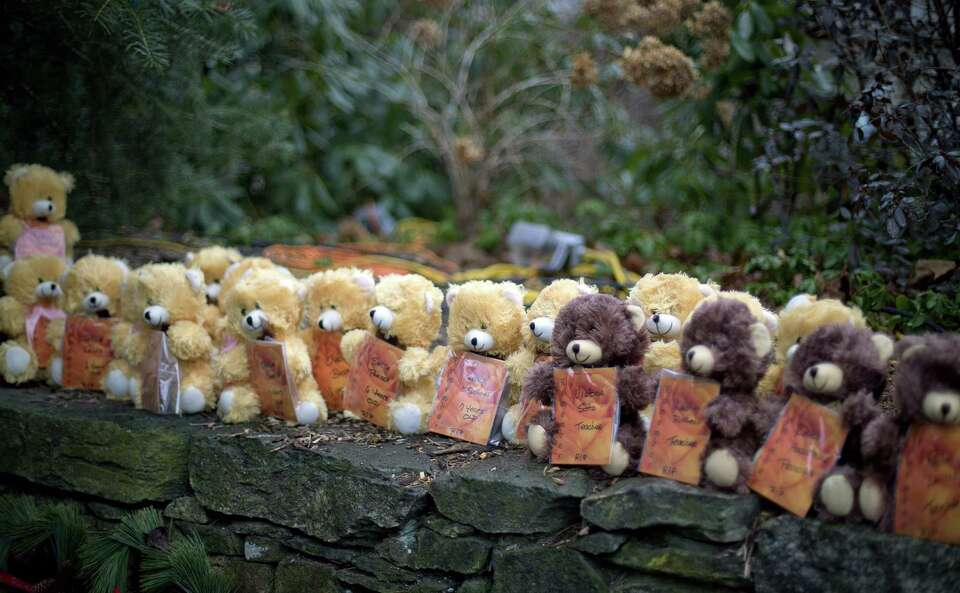 Teddy bears, each representing a victim of the Sandy Hook Elementary School shooting, sit on a wall